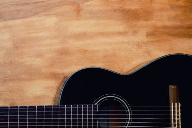 Body of a black guitar against a grungy wooden background, copy space for your text (retro toned), selective focus stock vector