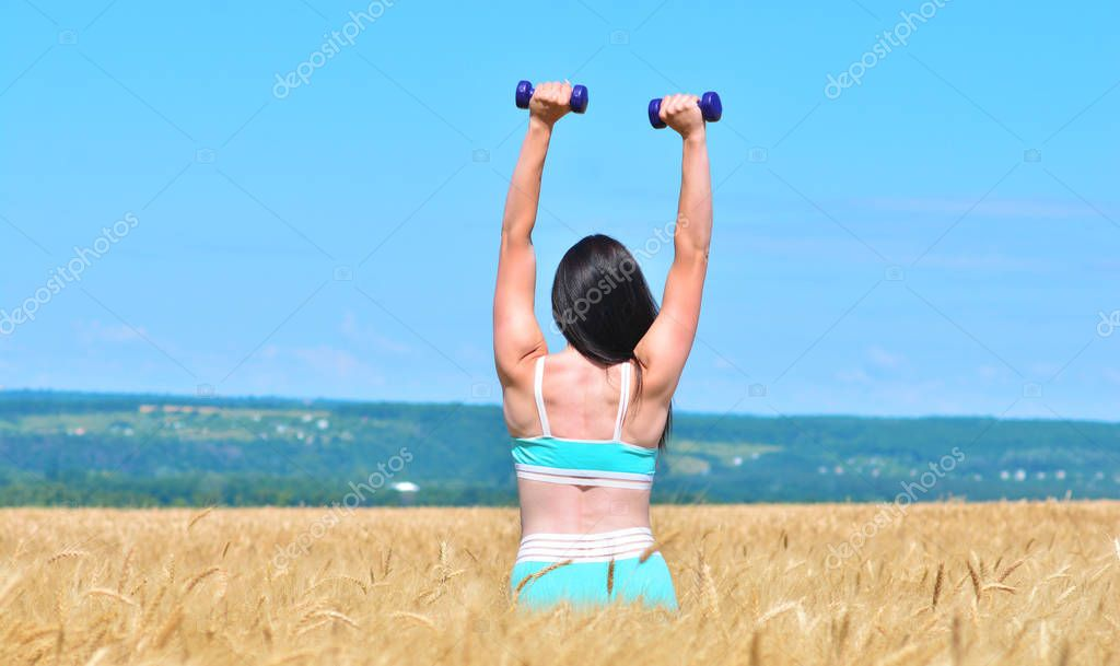 Sporty young woman takes hands up with dumbbells outdoors in a wheat field
