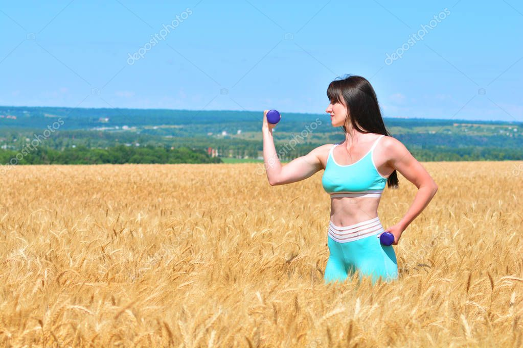 Sporty young woman doing exercise with dumbbells outdoors in a wheat field