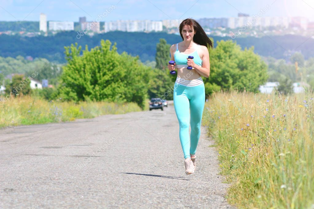 Training concept background. Fitness girl running with dumbbells in hands outdoors far from the city.