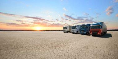 Büyük boş otoparkta dört vagon taşıyan kamyonlar. Kargo alımı veya ihracat fikri.