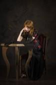 rothaariges Mädchen in dunkler Kleidung sitzt am Tisch.