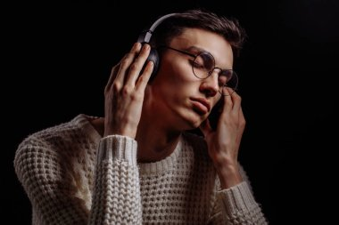 Young man wearing glasses and headphones listening to music on black background