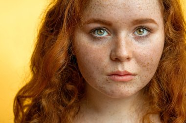 Close-up of beautiful red-haired freckled girl with loose curly hair