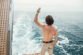 Rear view of young man sitting at edge of yacht looking at sea