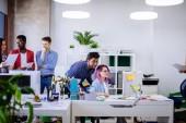 Skupina mladých lidí v moderní kanceláři mají diskuse o novém projektu