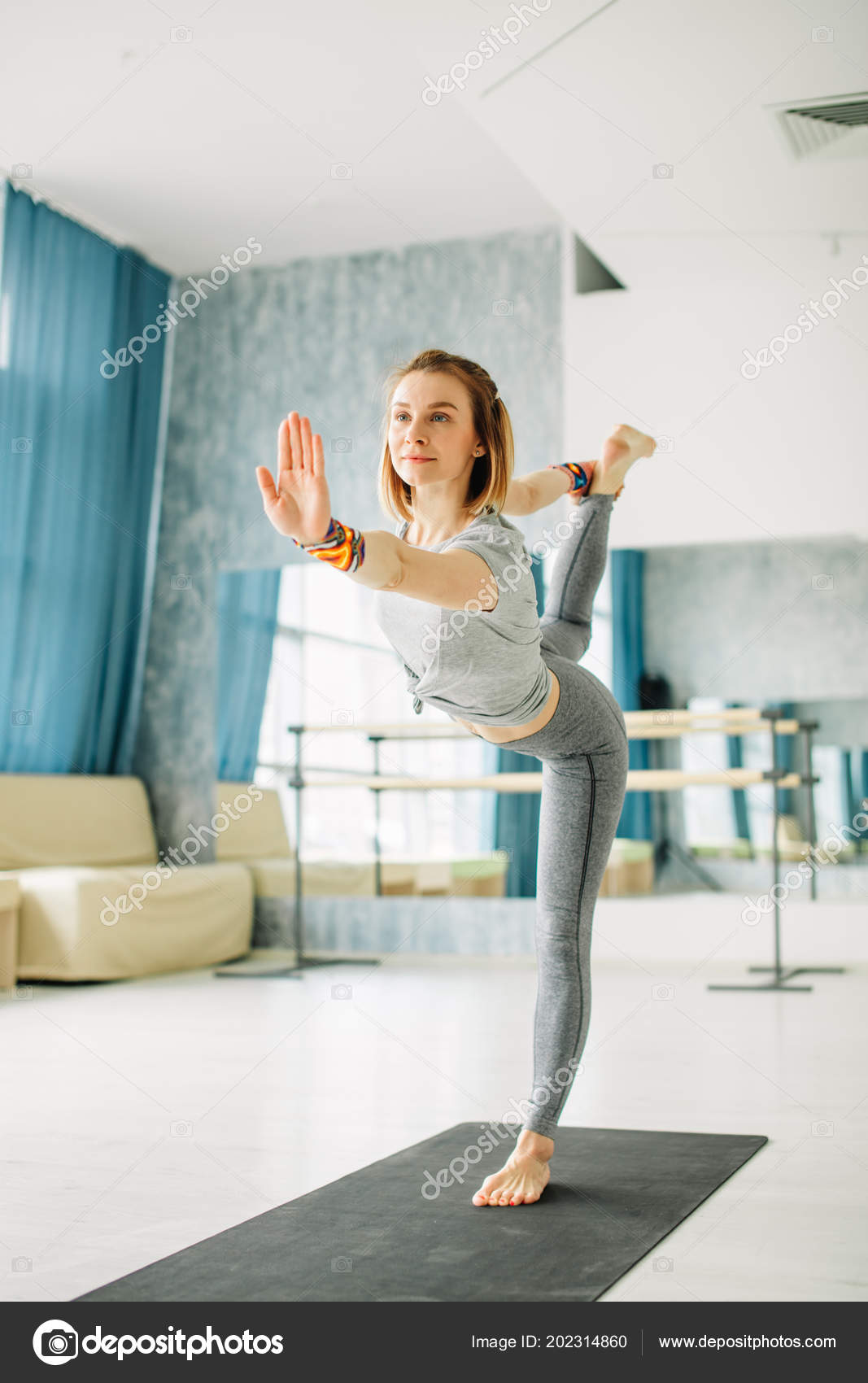 Young fit woman doing a yoga pose standing with one leg raised up. 37