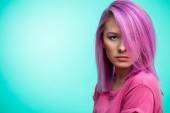 Attractive girl with pink hair, dressed in casual pink cloth on blue background.