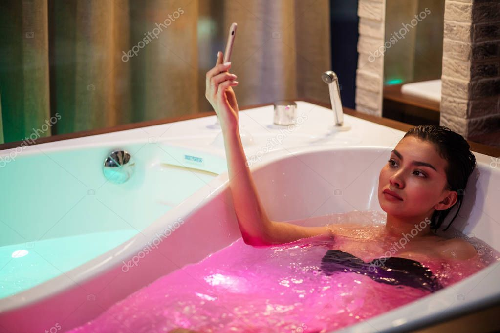 Woman having bath with color therapy and taking photo.
