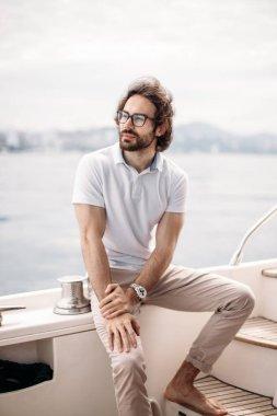 Smiling adult caucasian bearded sailor navigating in Caribbean sea