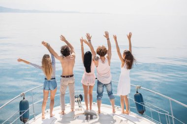 Rear view of friends celebrate on sailboat in ocean, arms raised.