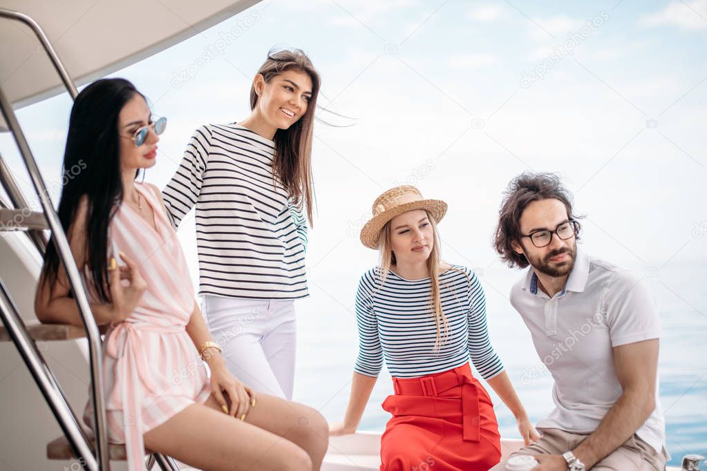 Travel, seatrip, friendship and people concept - friends sitting on yacht deck