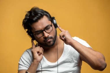 close up portrait of good-looking Indian model enjoying listening to the music