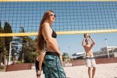 ženské beach volejbalový hráč skákání dosahuje volejbal přes net