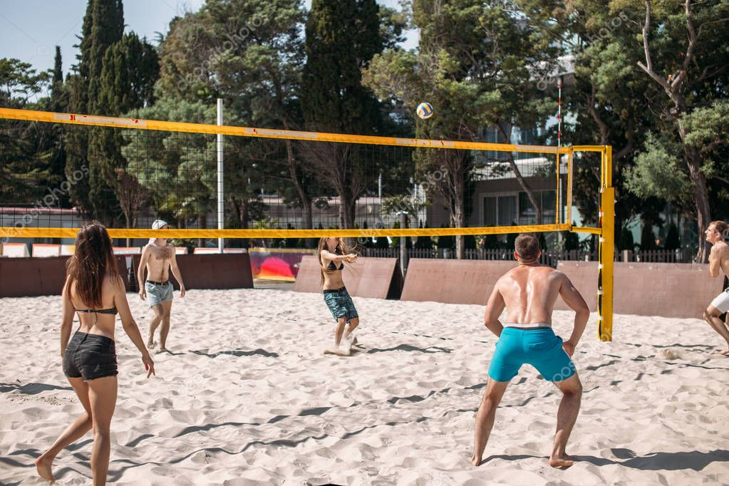 Group young caucasian friends playing volleyball on beach on summer vacation