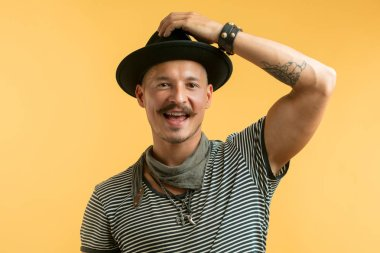 Happy man with moustache wearing hat isolated over yellow background.
