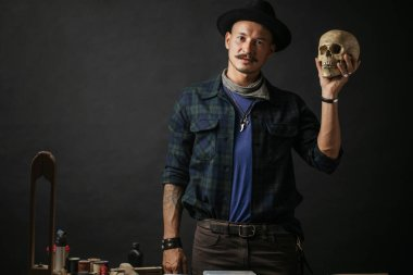 Stylish man with mustache wearing hat and holding scull posing indoors