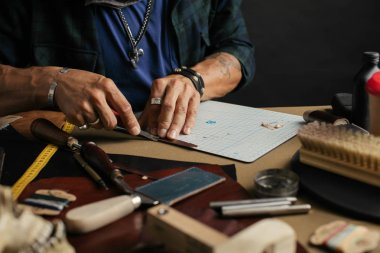 Leather goods master and handmade leather wallets. Workflow in the workshop.