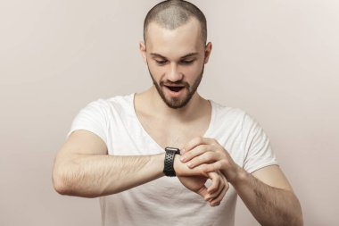 happy young man learning to use smartwatch