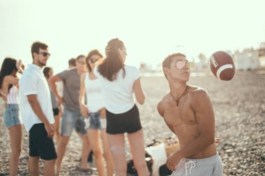 young friends having fun and dancing on beach during sunset