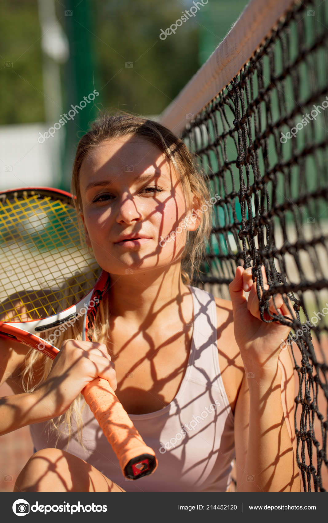 Portrait of young beautiful blonde sportswoman with tennis racket sitting  near tennis net reflecting on her body. Sport a1c5329864