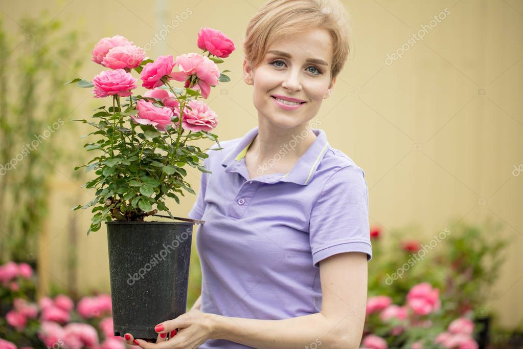 Beautiful young woman with roses posing in garden