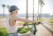 Fotografie Young girl wearing helmet and protective glasses sits near electric bicycle