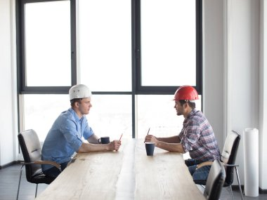 Confident constructors are solving problems while sitting at the table in the modern office room . side view photo stock vector