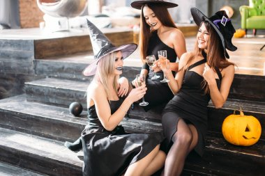 Three girls sit and clink glasses with champagne