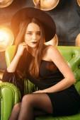 Fotografia Alla moda halloweens modello strega che si siede alla sedia