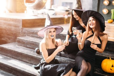 Halloween party. Three girls in costumes for a party for Halloween posing with glasses of champagne in their hands. They clink glasses
