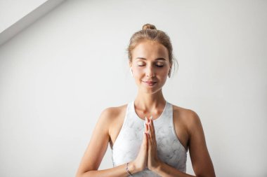 Young attractive Yoga teacher female greeting at the begining of practicing yoga