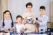 Fotografie vzdělávání, věda, technologie, děti a lidé koncept, příjemný mladý inženýr matka ukazuje její děti pomocí přenosného počítače, jak sestavit a program obyčejný robot sady