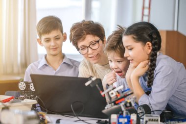 Happy children learn programming using laptops on extracurricular classes