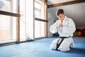 Fényképek Karate kimonó ember ül térdre a harcművészetek edzőteremben emelet