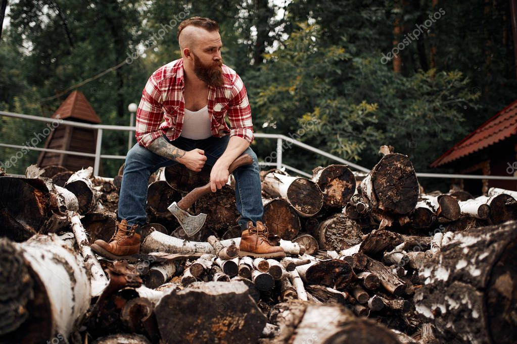 Man sitting on firewoods. Woodcutter with axe resting after work
