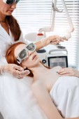 Woman getting laser face treatment in medical center, skin rejuvenation concept