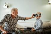 ragazzo e suo nonno utilizzando occhiali vr sul sofà a casa