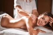 Krásná mladá žena dostává masáž těla v lázeňském salonu