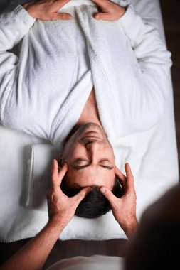 Young man receiving massage at spa salon, top view