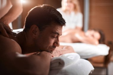 Young couple receiving a back massage in a Spa center
