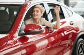 Přešťastný řidič žena usmívající se a ukazuje nový klíč, zatímco sedí v autosalonu