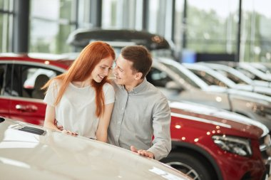 Happy couple chooses first family car to buy in a showroom