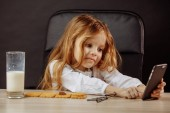 Fotografie Adorable little girl playing with smartphone in Daddy s office