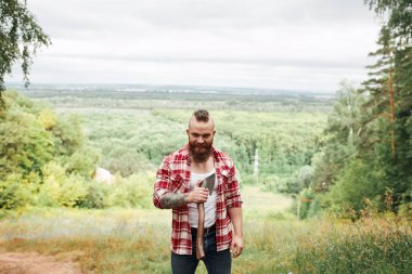 bearded lumberjack worker standing in forest with axe