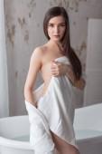 Junge Frau im weißen Bademantel sitzt an der Seite des freistehenden weißen Bades