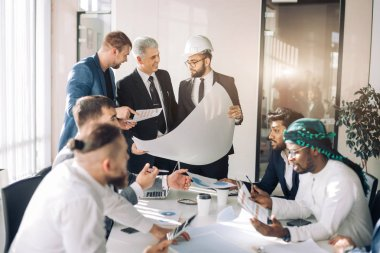 Interracial group of male architects and builders are engaged in lively discussion of the budget and building plan for a new object. stock vector