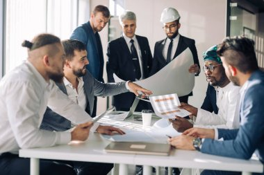 Multiracial group of constructors, builders, engeneers and architects discussing blueprint at office. All men are dressed in business suits, and white shirts, one of them wears hardhat on head stock vector