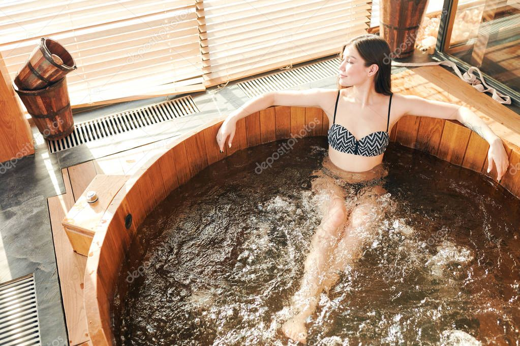 Brunette woman relaxing in jacuzzi in spa center with panoramic windows