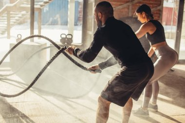 Woman and man in gym functional training with battle rope exercising